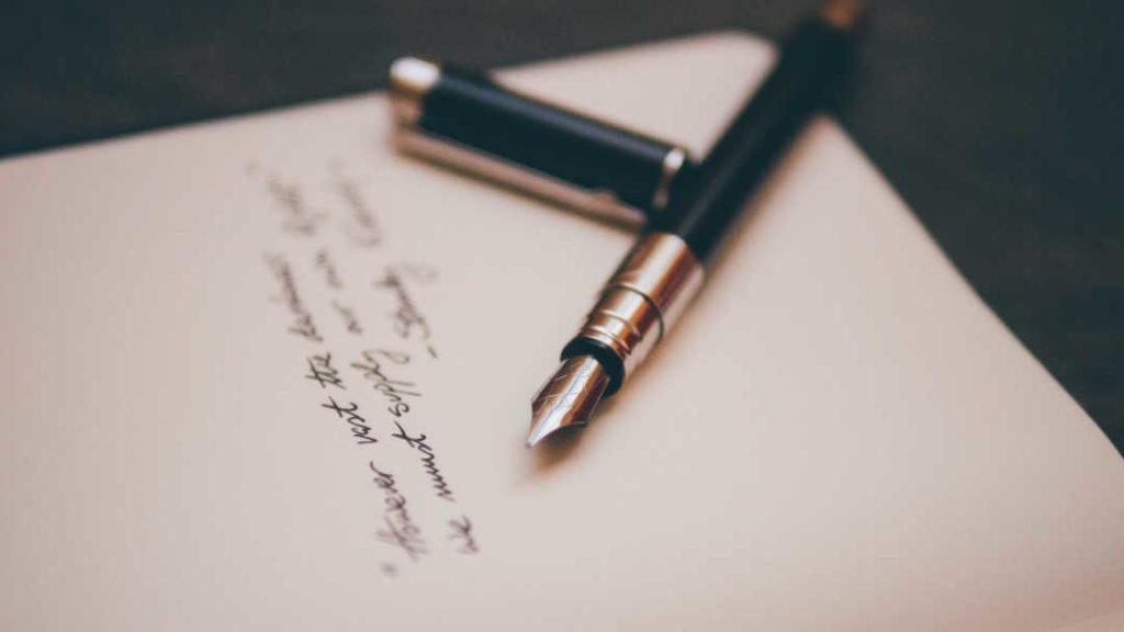 Pluma y carta para escribir una carta de motivación para un máster