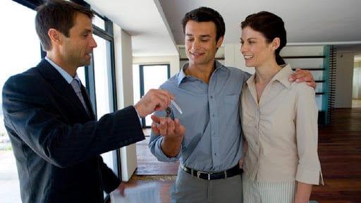 Agente inmobiliario entregando llaves de una casa